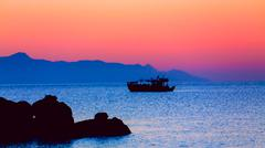 fisherman boat at  sunset - stock photo