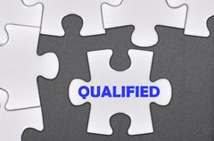 Jigsaw puzzle written word qualified Stock Photos
