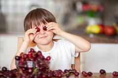Cute little boy, eating cherries at home in the kitchen, making funny faces Kuvituskuvat