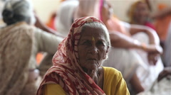 Old Indian woman sitting on the floor in the Ashram among other widows. Stock Footage