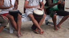 Unidentified man playing on drum at the beach Stock Footage