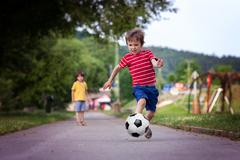 Two cute little kids, playing football together, summertime - stock photo