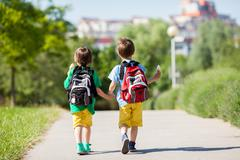 Two adorable boys in colorful clothes and backpacks, walking away Stock Photos