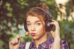 Portrait of hipster girl with headphones and lollipop. Stock Photos