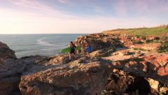 Young Surfers Walking On Edge Of Sea Rocks Cliffs Aerial Vacation Happiness Stock Footage