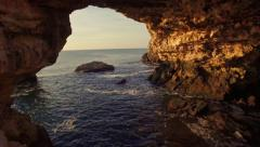 Aerial Fly Under Sea Rocks Beautiful Ocean Cliffs Cave Blue Water Sunrise Golden Stock Footage