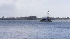 SPORTFISHERMAN MOTORBOAT anchored in bay - stock footage