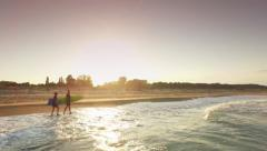 Young Adventurous Surfer Couple Walking On Ocean Beach At Sunset As Waves Cover Stock Footage
