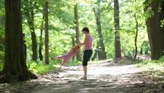 Young mother with little daughter walking in the park - stock footage