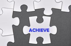 Jigsaw puzzle written word achieve Stock Illustration