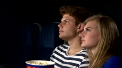 Couple feeding each other at the cinema. Close up Stock Footage