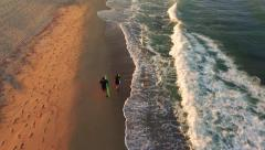 Aerial Surfers Walking On Beach At Sunset Waves Covering Yellow Sand Happy Stock Footage