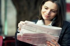 Young woman reading ads in newspaper sitting in cafe NTSC Stock Footage