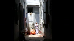 Older Indian women wash up and wash the dishes in running water in the courtyard Stock Footage