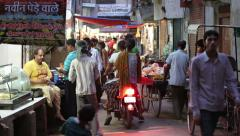 Pedestrians, rickshaws and motorcycles on a narrow shopping street in India - stock footage