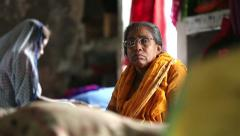 An elderly Indian woman sitting on her bed in a dormitory at the Ashram. Stock Footage