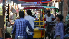 Pedestrians, rickshaws and motorcycles on a narrow shopping street in India Stock Footage