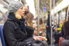 Woman traveling by subway full of people. Stock Photos