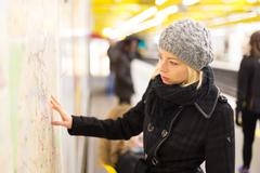 Lady looking on public transport map panel. - stock photo