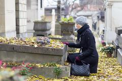 Solitary woman visiting relatives grave. - stock photo