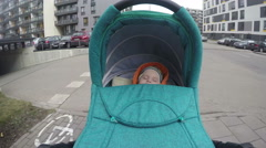 Baby sleep in his pushchair stroller while walking in street. 4K Stock Footage