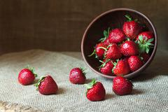 Strawberry natural healthy nutrition organic food in rustic clay dish on vintage - stock photo
