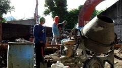 Workers shovel concrete mix Stock Footage