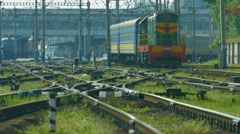 Train moving to the station. Locomotive pulls a lot of wagons. - stock footage