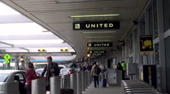 Passengers at the outdoors Departure level of LaGuardia Airport Stock Footage