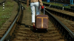 Girl with a suitcase goes on rails. Stock Footage