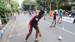 City children rollerskating on closed Street, playing handball , editorial Stock Footage