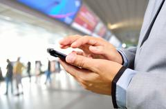 Business Man using Mobile Phone in Modern Train Station - stock photo
