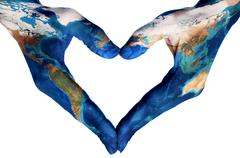 hands forming a heart patterned with a world map (furnished by NASA) - stock photo
