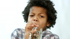Curly african learning to play the trumpet. - stock footage