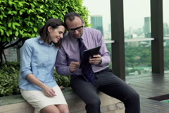 Happy businesspeople watching movie on tablet computer on the roof terrace NTSC. Stock Footage