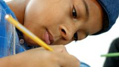 Black boy draws, face close up. - stock footage