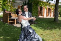 Newly married couple dancing in field. Outdoor portrait of bride and groom Stock Photos