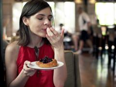 Beautiful woman eating tasty yeast-cake in cafe NTSC Stock Footage