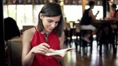 Young, pretty woman reading book sitting in cafe in city HD Stock Footage