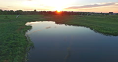 Aerial view of small pond in grass land at sunset. Stock Footage