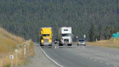 Two oncoming trucks on the highway in British Columbia, Canada. - stock footage