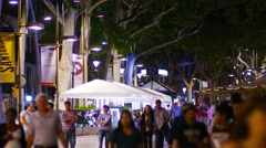 Stock Video Footage of BARCELONA, multiple tourists strolling on Rambla boulevard at night.