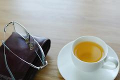 On a table a cup with tea and a purse. - stock photo
