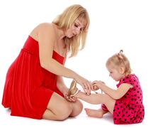 Stock Photo of Mom helps young daughter to wear a slipper