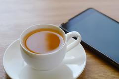 On a table a cup of tea and the smart phone. - stock photo