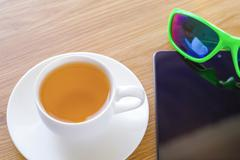 Green tea, reflexion in sun glasses and the smart phone. - stock photo