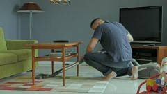 Man cleaning house, vacuum cleaning under table - stock footage