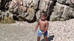 Zoom in toddler plays with a box at the seaside Stock Footage