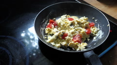 Making scrambled eggs adding herbs and pepper Stock Footage