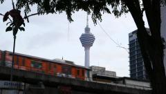 Elevated LRT line against KL Tower, train pass by to Masjid Jamek station Stock Footage